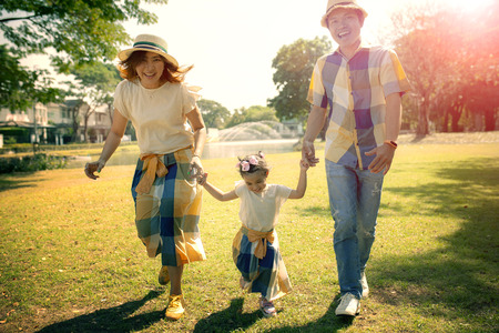 padre asiatico madre e figlia felicità emozione nel verde parco pubblico Archivio Fotografico