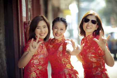 group of asian woman wearing chinese tradition clothes toothy smiling face happiness emotion and hand sign i love you