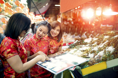 three asian woman wearing chinese tradition clothes happiness touring in yaowarat road one most popular traveling and famous street food in bangkok thailand Stock Photo