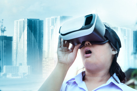 younger woman wearing virtual reality glasses with surprising face standing outdoor against modern city building  background