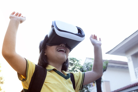 children wearing virtual reality glasses with fun and surprising face standing  outdoor Foto de archivo - 119350605