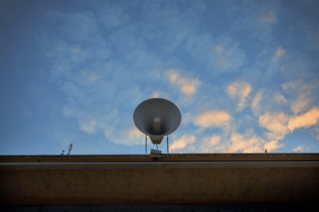 loudspeaker on building roof against beautiful morning colorful sky Stock Photo