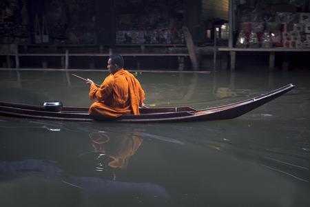 ratchaburi thailand - january1,2019 : thai monk sailing boat in dumneonsaduak canal ,floating market one of most popular traveling destination in  ratchaburi thailand Editorial