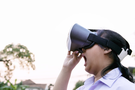 younger woman wearing virtual reality glasses with surprising face standing outdoor