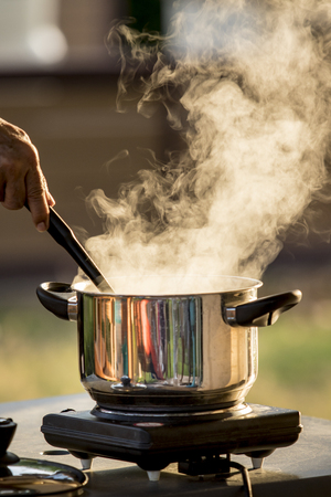 steam flowing from cooking pot against beautiful morning light