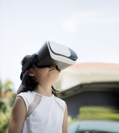children wearing virtual reality glasses with fun and surprising face standing  outdoor Stock Photo