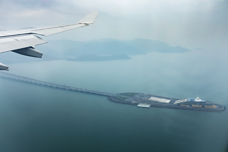 aerial view from plane window of hong kong - juhai - macau bridge crossing ocean harbor
