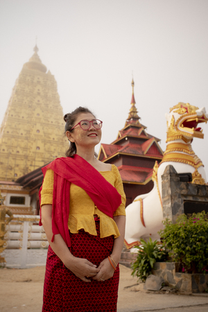 asian woman toothy smiling face standing in front of buddhism pagoda in kanchanaburi one of most popular traveling destination in thailand