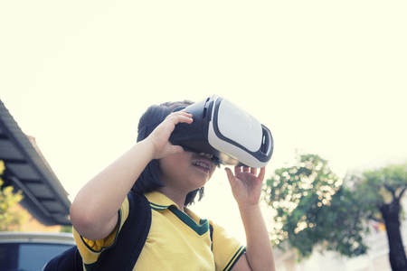 children wearing virtual reality glasses with fun and surprising face standing  outdoor Banco de Imagens
