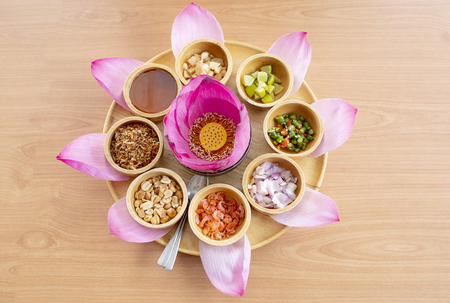 pink lotus petal flower decorated and is part of thai snack food on clear wood table Banco de Imagens