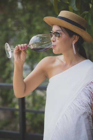 portrait of beautiful asian younger woman drinking red wine in elegance wineglass Stockfoto