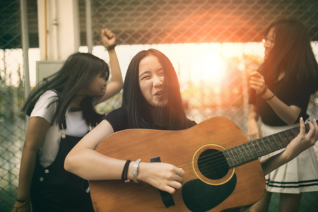 group of asian teenager standing outdoor plying spanish guitar and dancing with happiness emotion Stockfoto