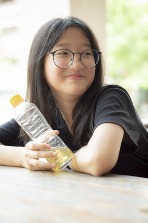 asian teenager smiling face holding pastic bottle in hand Banco de Imagens - 121579076