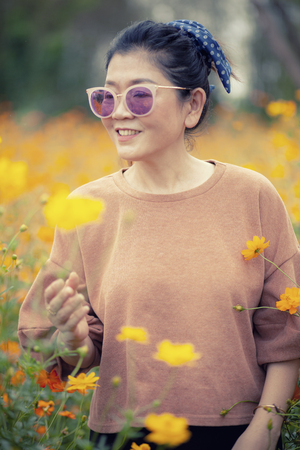 portrait smiling face asian woman standing with happiness emotion in yellow cosmos blooming field Stockfoto