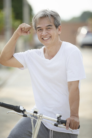 middle age asian man toothy smiling face happiness emotion exercise by riding bicycle in home village street Imagens - 121579340