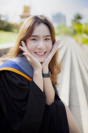 asian woman toothy smiling face with happiness emotion wearing university graduation suit
