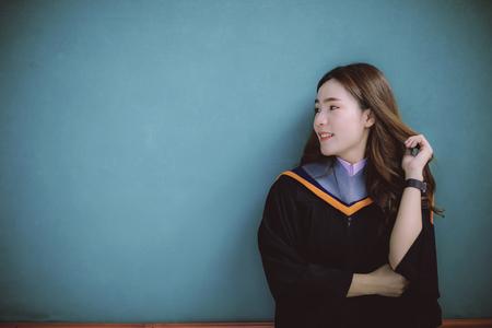 Frau, die einen Universitätsabschlussanzug trägt, der gegen eine klare blaue Wand zahniges lächelndes Gesicht mit Glücksgefühlen steht