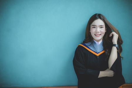 woman wearing university graduation suit standing against clear blue wall toothy smiling face with happiness emotion Imagens - 121579403