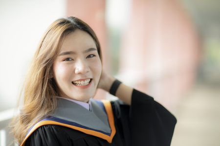 toothy smiling face of beautiful asian younger woman wearing university graduated clothes happiness emotion