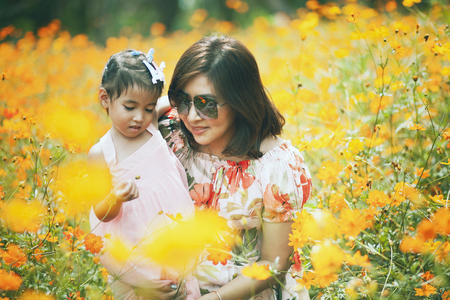 asian woman and little girl happiness emotion in yellow cosmos flower blooming field Imagens - 121580607