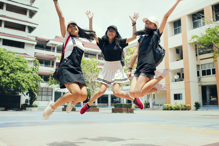 three asian teenager jumping mid air with happiness emotion against school building background Stockfoto