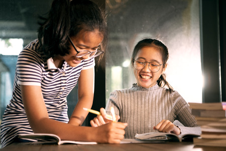 two asian girl laughing with happiness emotion doing school home work in living room Imagens - 123580943