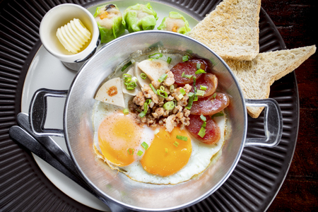 morning eggs fried with pork and bread in metal dish ready to eating Stockfoto