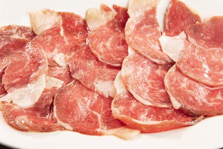 sliced of  beef arranged on plain plate