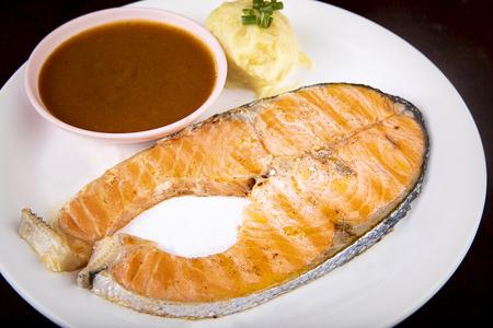 sliced of salmon steak arranged on white plate ready to eating Imagens