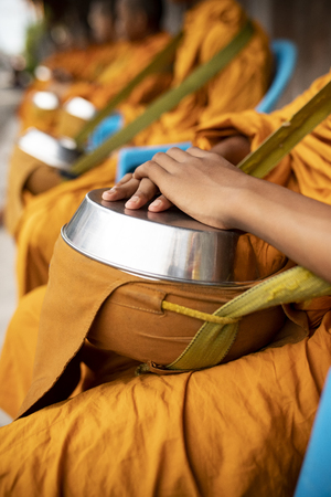 group of thai monk wearing yellow clothes and holding buddhist bowl waiting for buddhist people offering morning food