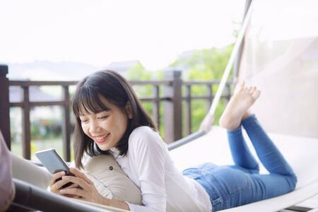 asian younger woman toothy smiling with happiness holding smart phone in hand ,relaxing lifestyle