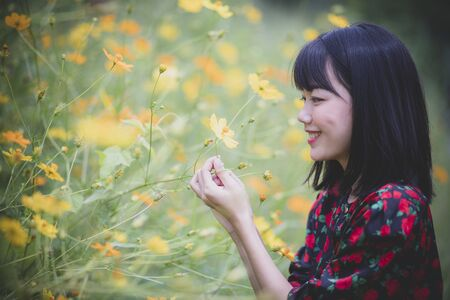 portrait of asian younger woman model pose in yellow flower blooming field Zdjęcie Seryjne