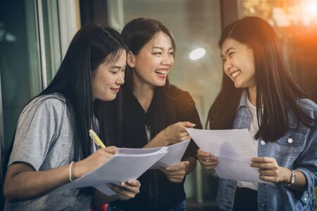 asian younger woman freelance talking with toothy smiling face in home office