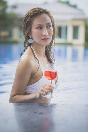 bikini woman and glass of red beverage in swimming pool Zdjęcie Seryjne