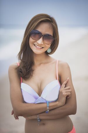 beautiful tan skin of asian younger woman wearing beach bikini  toothy smiling at sea beach