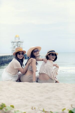 three beautiful asian younger woman laughing with relaxing emotion at vacation sea side