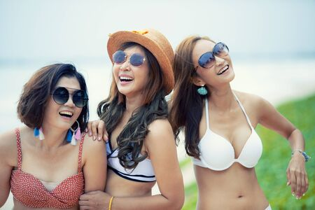 group of cheerful asian younger woman  wearing beach bikini laughing with happiness emotion