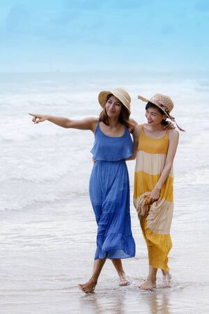 portrait of young asian woman with happiness emotion wearing beautiful dress walking on sea beach and laughing joyful use for people relaxing vacation on destination Zdjęcie Seryjne