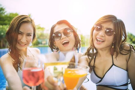 three younger asian woman happiness drinking beverage in waer swimming pool