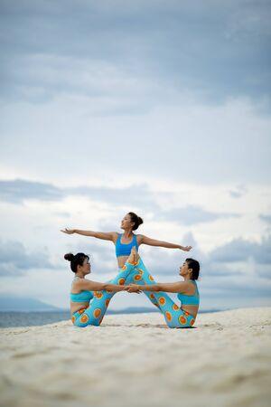 three woman playing yoga pose on sand beach Zdjęcie Seryjne