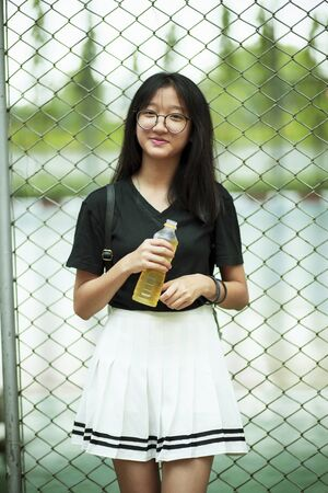 asian teenager smiling face holding pastic bottle in hand