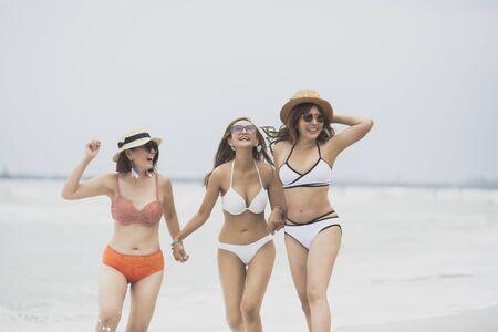 three asian woman bikini relaxing on vacaton beach