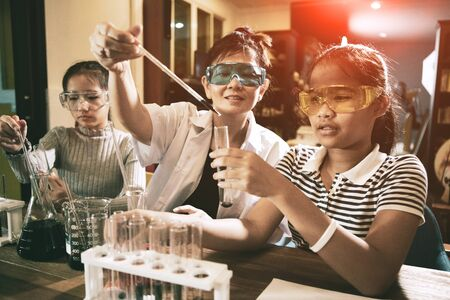 asian teacher and student in school science laboratory room