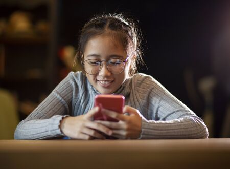 asian teenager reading message on smart phone screen with happiness smiling face