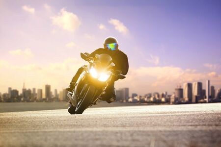 man riding sport motorcycle lean on curve road against urban skyline background Zdjęcie Seryjne