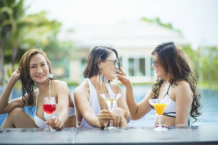 three younger asian woman happiness drinking beverage in wear swimming pool Zdjęcie Seryjne