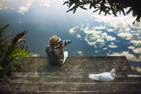 traveling man taking a photograph at old pier against beautiful blue sky reflection on water floor Zdjęcie Seryjne