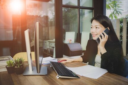 asian younger woman taking on mobile phone and computing in working office
