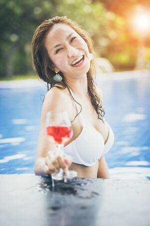 bikini woman and glass of red beverage in swimming pool 版權商用圖片
