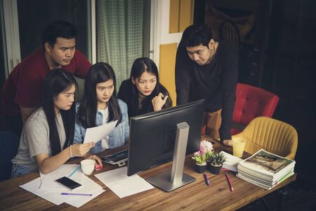asian freelance team looking to office computer with seriously face